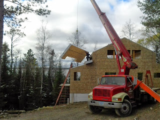 Crane installing SIPs on a timber frame home near ely mn, huisman