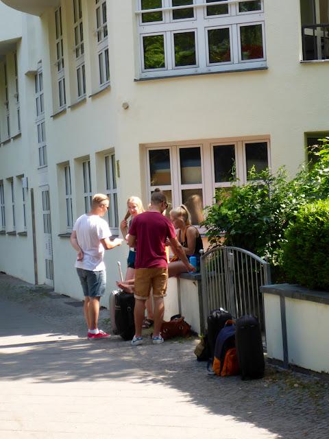 Jugendliche Rollkoffertouristen vor einem früheren Miethaus, Maybachufer 19