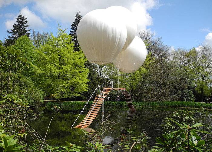 "French artist Olivier Grossetête used three enormous helium balloons to float a rope bridge over a lake in Tatton Park, a historic estate in north-west England. Oliver Grossetête created Pont de Singe, which means ""monkey bridge"", for the Tatton Park Biennial, which this year was themed around flight. Located in the park's Japanese garden, the structure comprised a long rope bridge made of cedar wood held aloft by three helium-filled balloons. The ends of the bridge were left to trail in the water. Though visitors weren't allowed to use the bridge, it would theoretically be strong enough to hold the weight of a person, according to Grossetête."