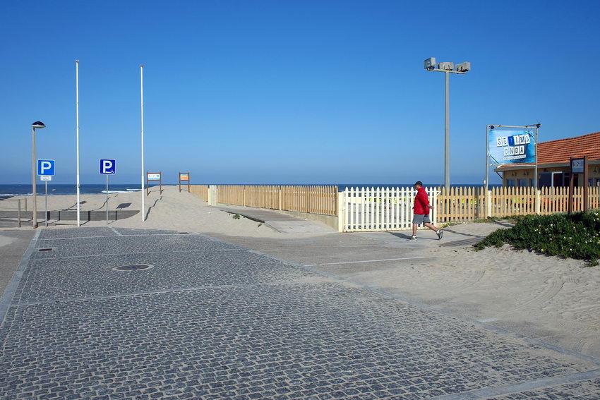 Parque junto ao mar. Um Bar à direita e dois mastros à esquerda. Uma pessoa a correr vinda da direita