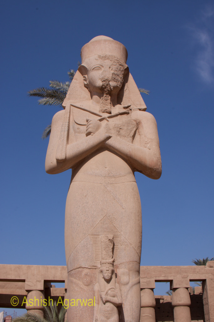 Front view of a statue of a pharaoh in the classical pose, inside the Karnak temple in Luxor
