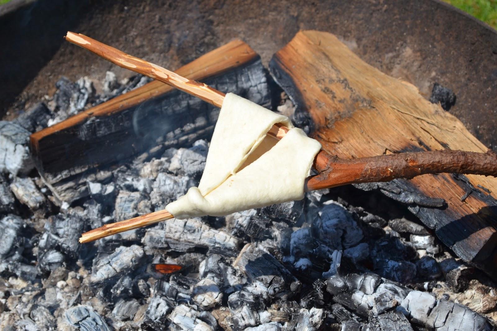 Vorkstok met croissantdeeg erom gevouwen boven een bak hete houtskool
