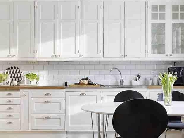 Biała kuchnia, czarne krzesła, graficzne dodatki, talerz z graficznym wzorem