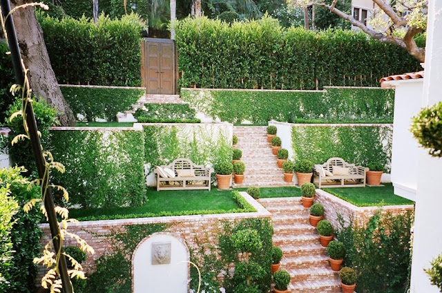 Brick stairs run through the tiered garden and lead to double carved garden doors