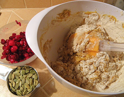 Half-Mixed Wet and Dry Ingredients, with bowl of Cranberries and bowl of Pumpkin Seeds