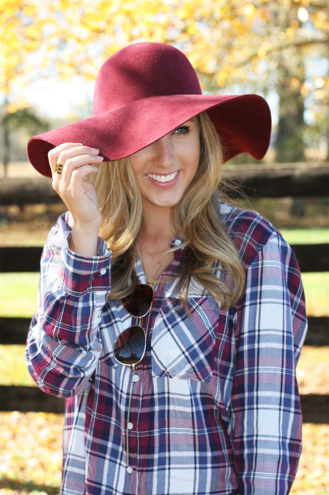 adorable-fall-headshot-with-floppy-hat-falling-leaves-and-a-farm