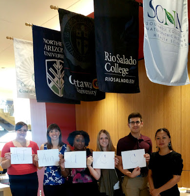 image of Communiversity at QC staff holding cards that read #IamUCC