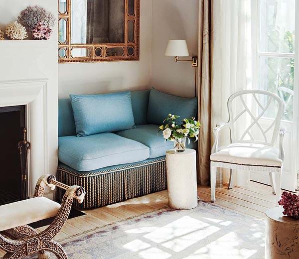 pequeño sofa esquinero azul ceruleo junto a la chimenea
