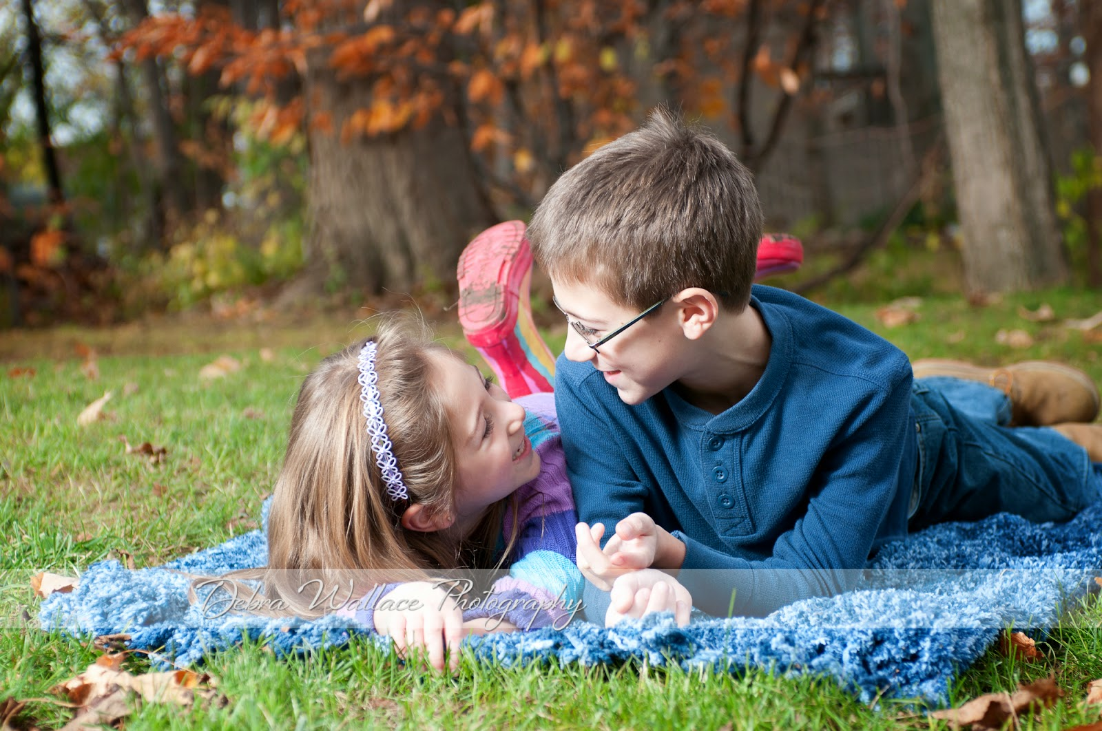 playful sibling portraits outside in the fall