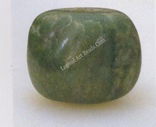 A Mayan jade bead, A. D. 200-500, carved from a water-worn pebble that has been slightly modified, perforated, and polish-ed.