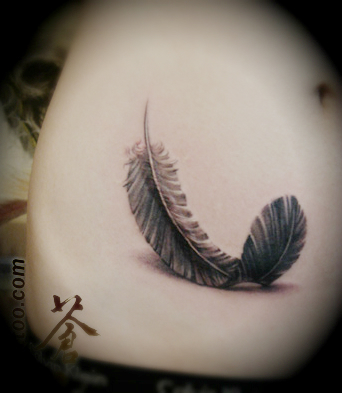 feather tattoo on the hip