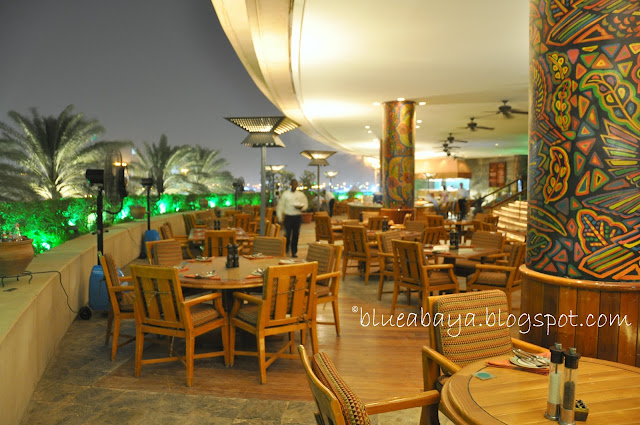 At the center of the restaurant there is a buffet island with salads and appetizers on one side and desserts on the other at the table the customers will