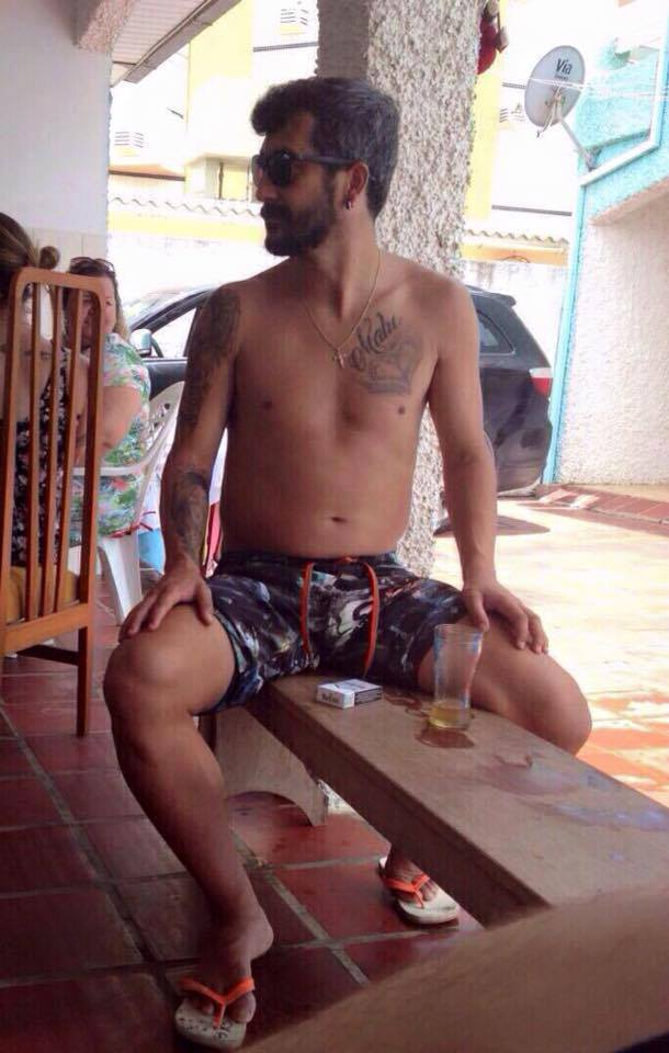 Douglas dos santos de bermuda tomando cerveja num banco
