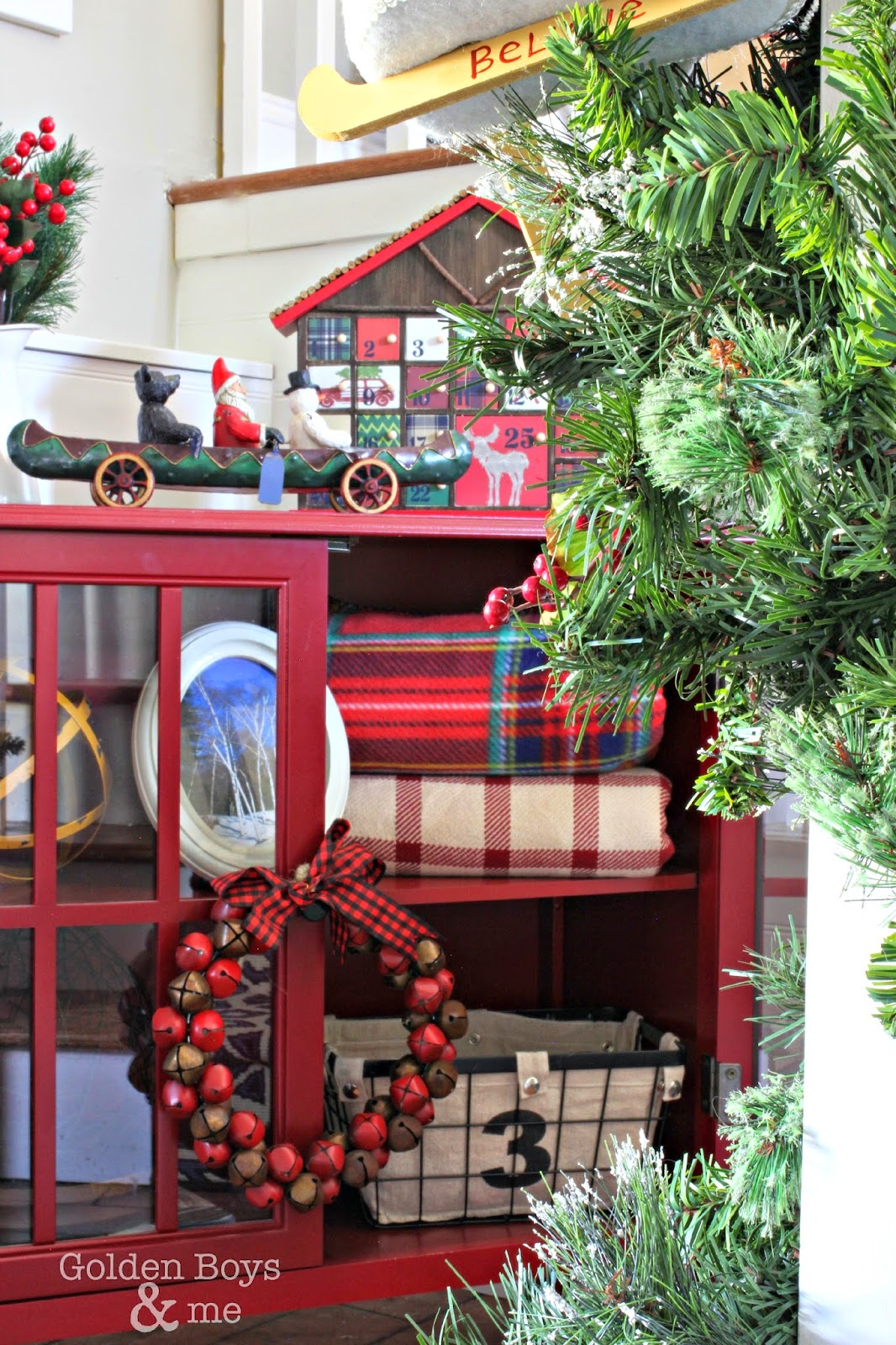Target red windham bookcase with plaid blankets in rustic Christmas entryway-www.goldenboysandme.com