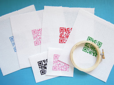 Picture of QR Code cross stitch pieces waiting to be stretched in hoops.