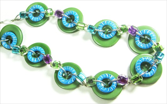Cool necklace has big green buttons, blue donut beads and small accent beads