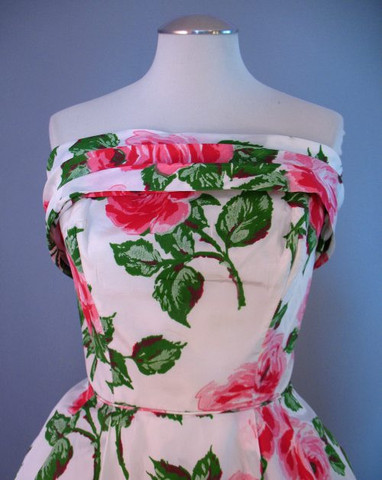The strapless bodice of this 1960s rose printed evening gown is decorated
