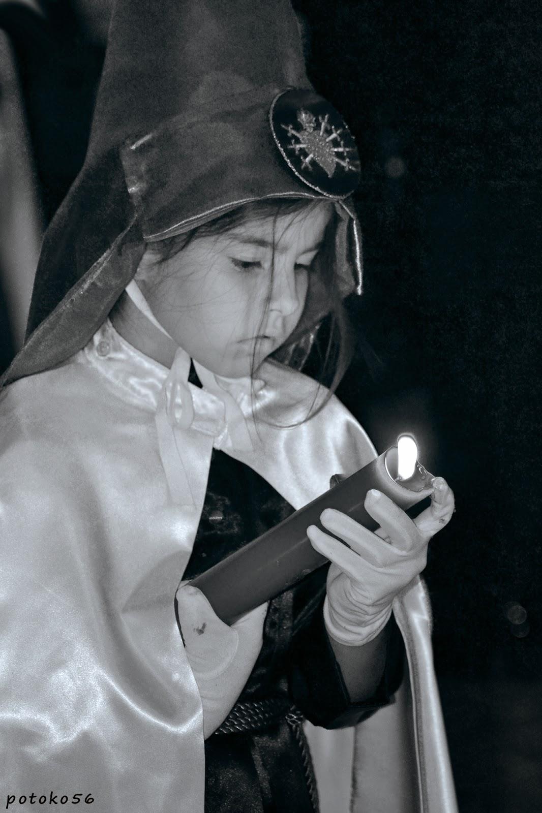 Semana Santa una penitente quitando cera a su cirio Rota