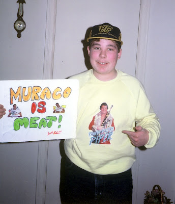 Young wrestling fan with sign and Rowdy Roddy Piper shirt and WWF hat