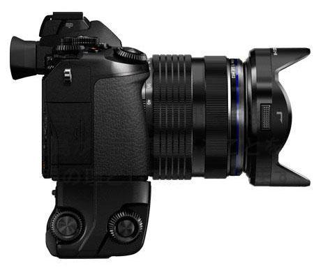 L'Olympus OM-D E-M1 fotografata di lato con zoom e impugnatura verticale