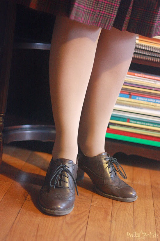 Brown lace-up shoes in front of a bookshelf