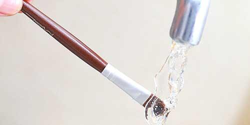 mojando brocha de makeup bajo el grifo