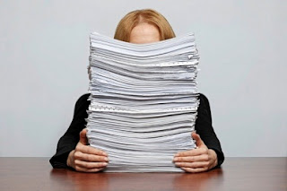 lady with large pile of papers on her desk