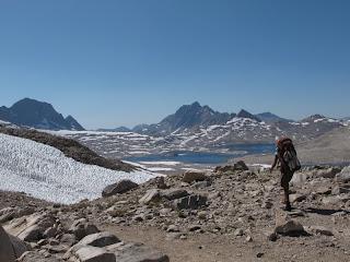 Eine zähe PCT Thru-Hikerin macht sich an den Abstieg ins Evolution Basin; im Hintergrund Wanda Lake