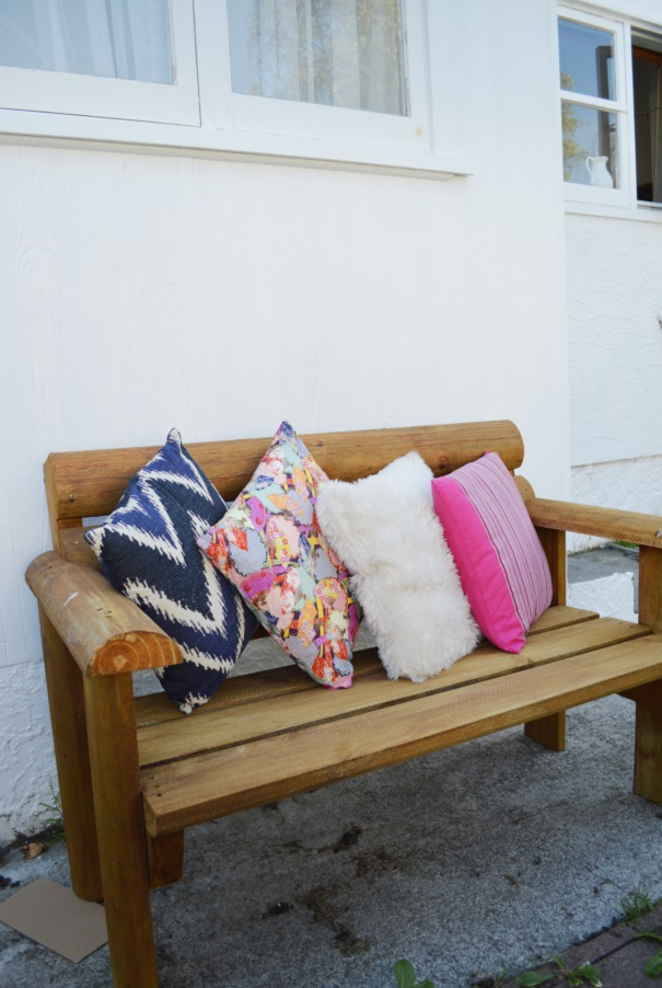 outdoor wooden bench with colourful pillows by Amy MacLeod