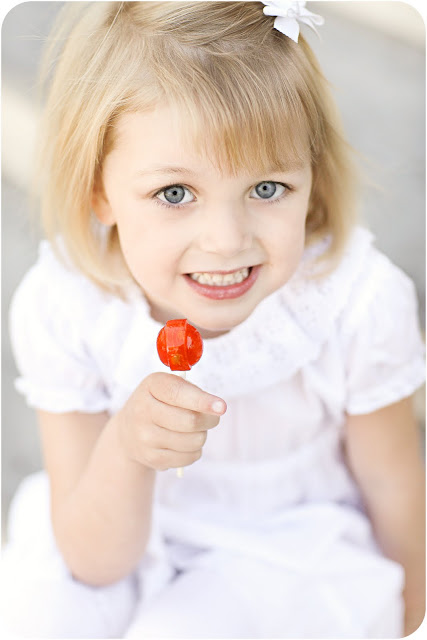 Child showing her reward a lollipop for posing for her family photographs