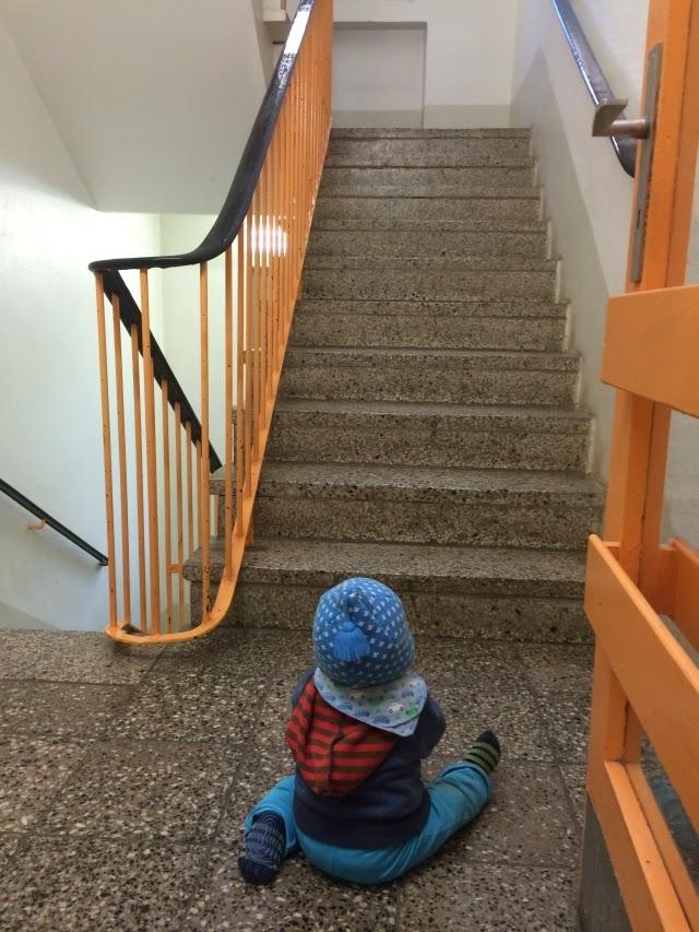 Kind sitzt im Treppenhaus