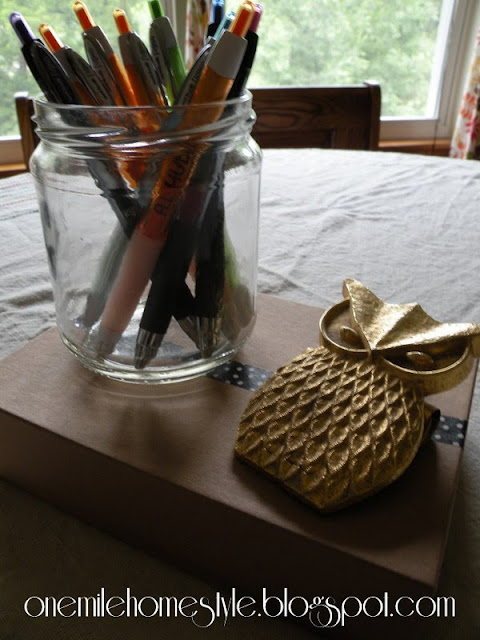 Old jar to hold pens and a box to hold notepads