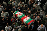 Iranians carry the flag draped coffin of a member of Revolutionary Guard, who was killed in an explosion at an ammunition depot west of Tehran together with 16 other Guard members.