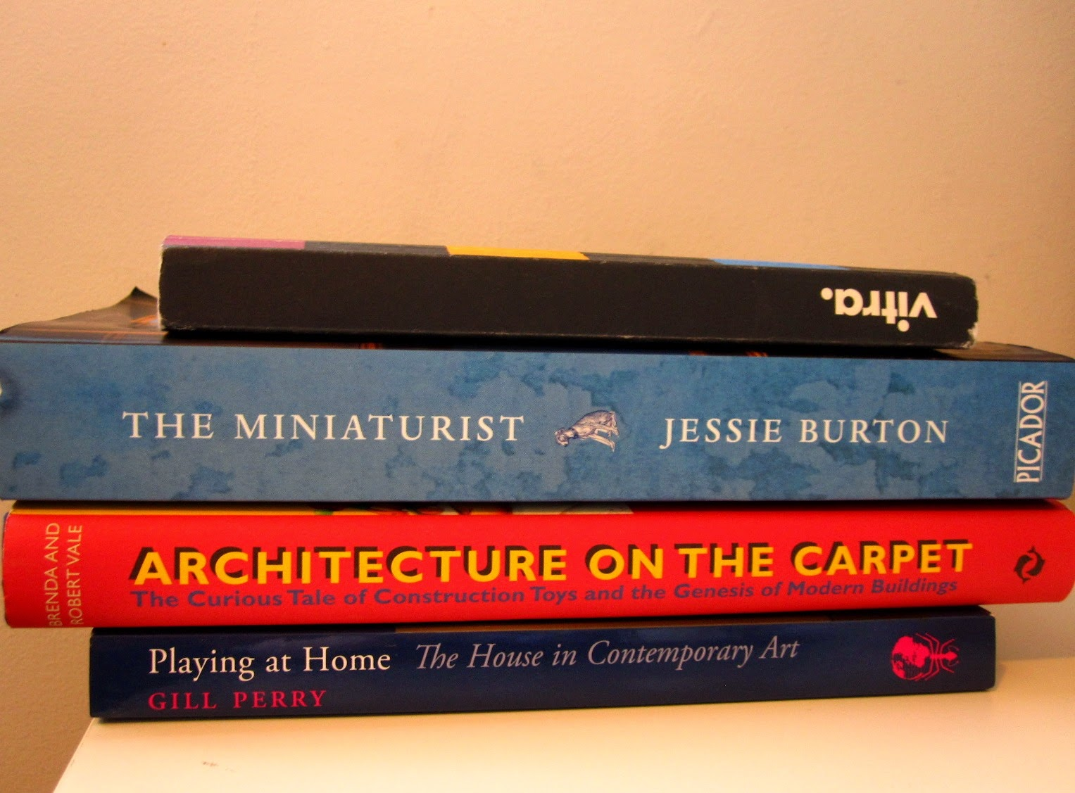 Four miniature-related books in a pile.