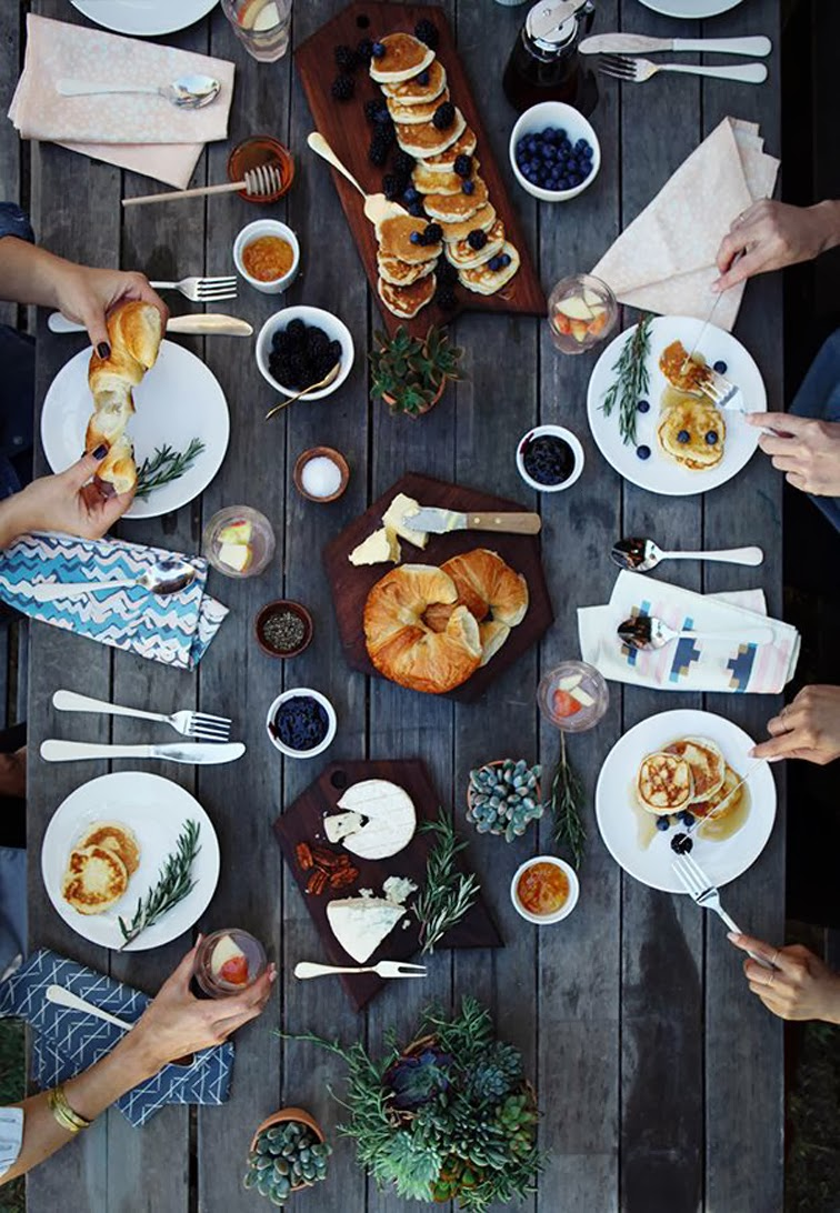 Breakfast table spread, croissants, pancake, berries