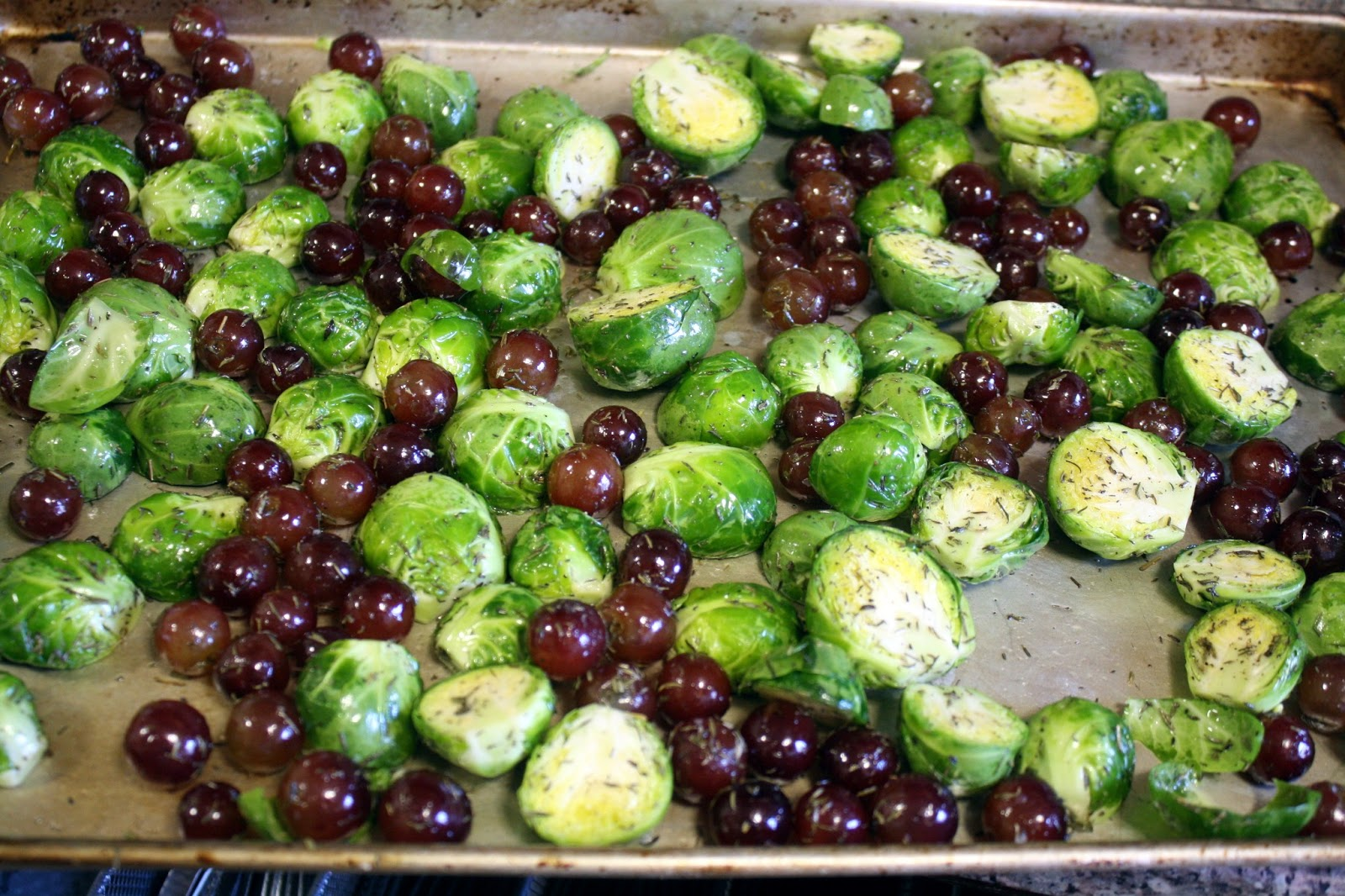 Tossed brussels sprouts and grapes on a baking sheet
