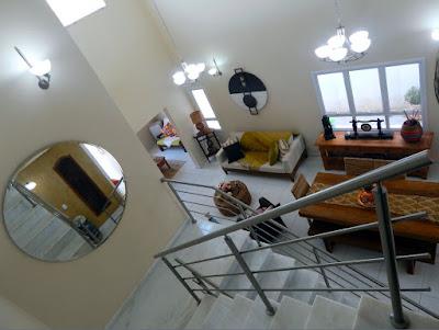 Visão a partir do mezanino, no topo da escada, sobre as salas de estar e jantar.