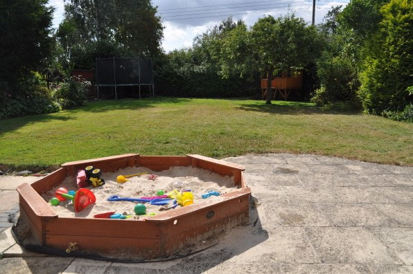 Morgan's Milieu | Home Exchange Membership Giveaway: Photo of a back garden with a playhouse and sandpit.