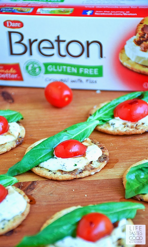 Caprese Crackers | by Life Tastes Good are gluten free, bite sized morsels of deliciousness! Topped with a garlic and herb cheese spread, fresh basil leaves, tomatoes, and a drizzle of balsamic dressing, these appetizer bites are tasty any time of day, and especially perfect for a party, as they are easy to make and so enjoyable to eat!