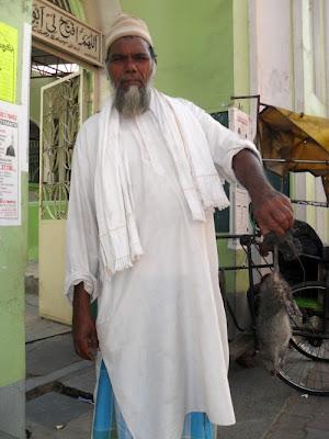 индус держит мертвую крысу в руках