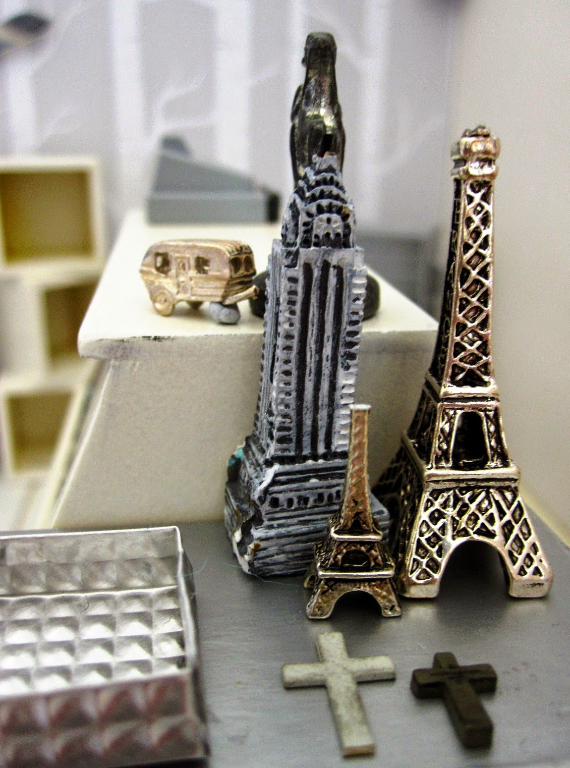 Close up of  a modern dolls' house miniature display of model buildings: an Eiffel Tower in two sizes, plus an Empire State Building. In front are two grey crosses and to the left is a grey metal tray.