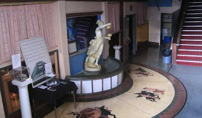 Colorful terrazzo floors with inlays and a plaster statue of a woman, after a Green classical figure