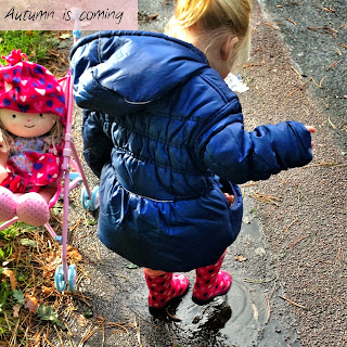 Toddler wearing wellies splashing in a puddle with a doll in hat and gloves