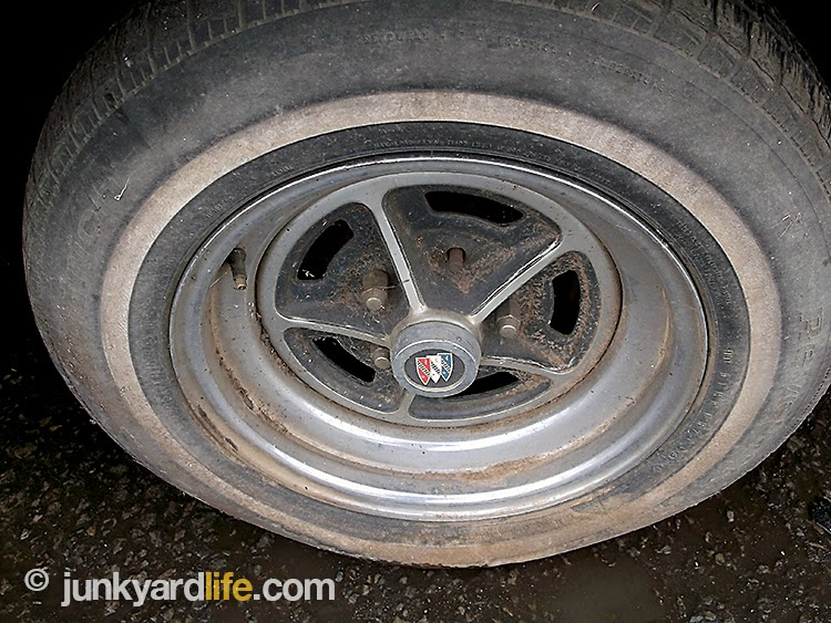 1977 Buick Regal wears four factory rally rims in the scrap yard.