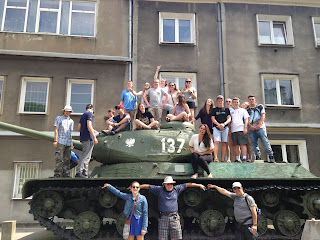students pose with world war two tank