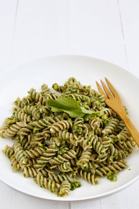 A plate with pesto pasta on a white wooden background