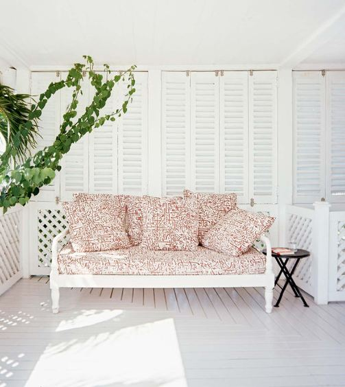 White porch with a black side table and a white daybed with red and white patterned cushions and pillows
