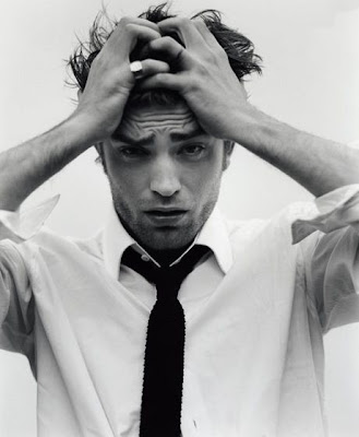 Actor Robert Pattinson holding his head and frowning, unhappily