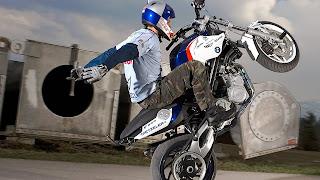 Foto met motorrijder die een kunstje laat zien op achterwiel