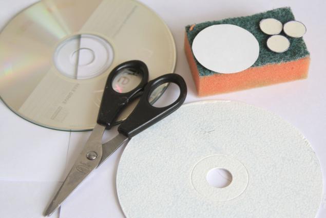 la parte central del cd que tiene un hoyito la tapamos con un circulo en cartulina blanca y pegamos sobre el cd